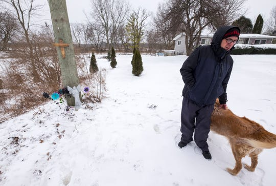 Dave Warf stands with his dog Sammy near a memorial he set up for Kevin Anderson Jr. Wednesday, Feb. 13, 2019 at his home in Fort Gratiot. Dave and his wife, Mary, found the body of Kevin Anderson on their property in the ditch by the road Sunday morning.
