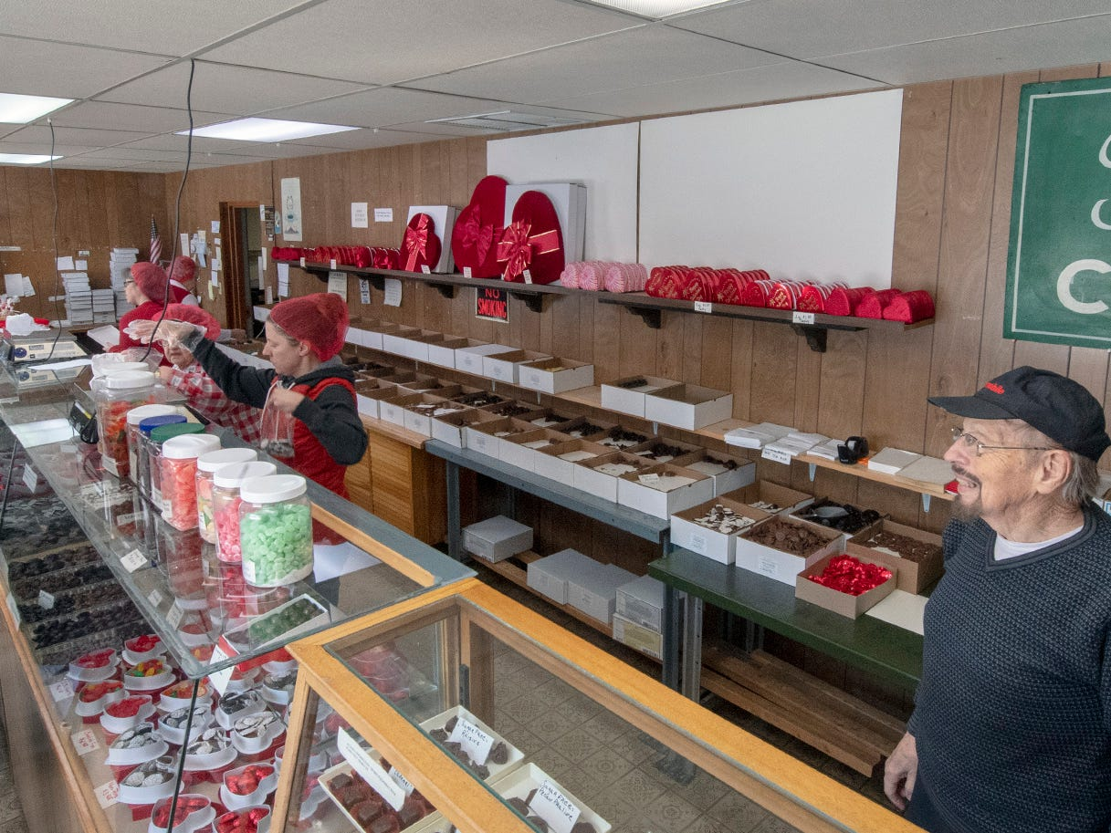 Robert Fitzkee, right, overlooks a line of workers serving customers Wednesday at Fitzkee's Candies. His mother, Crena, started the candy business in 1934 in a home nearby.