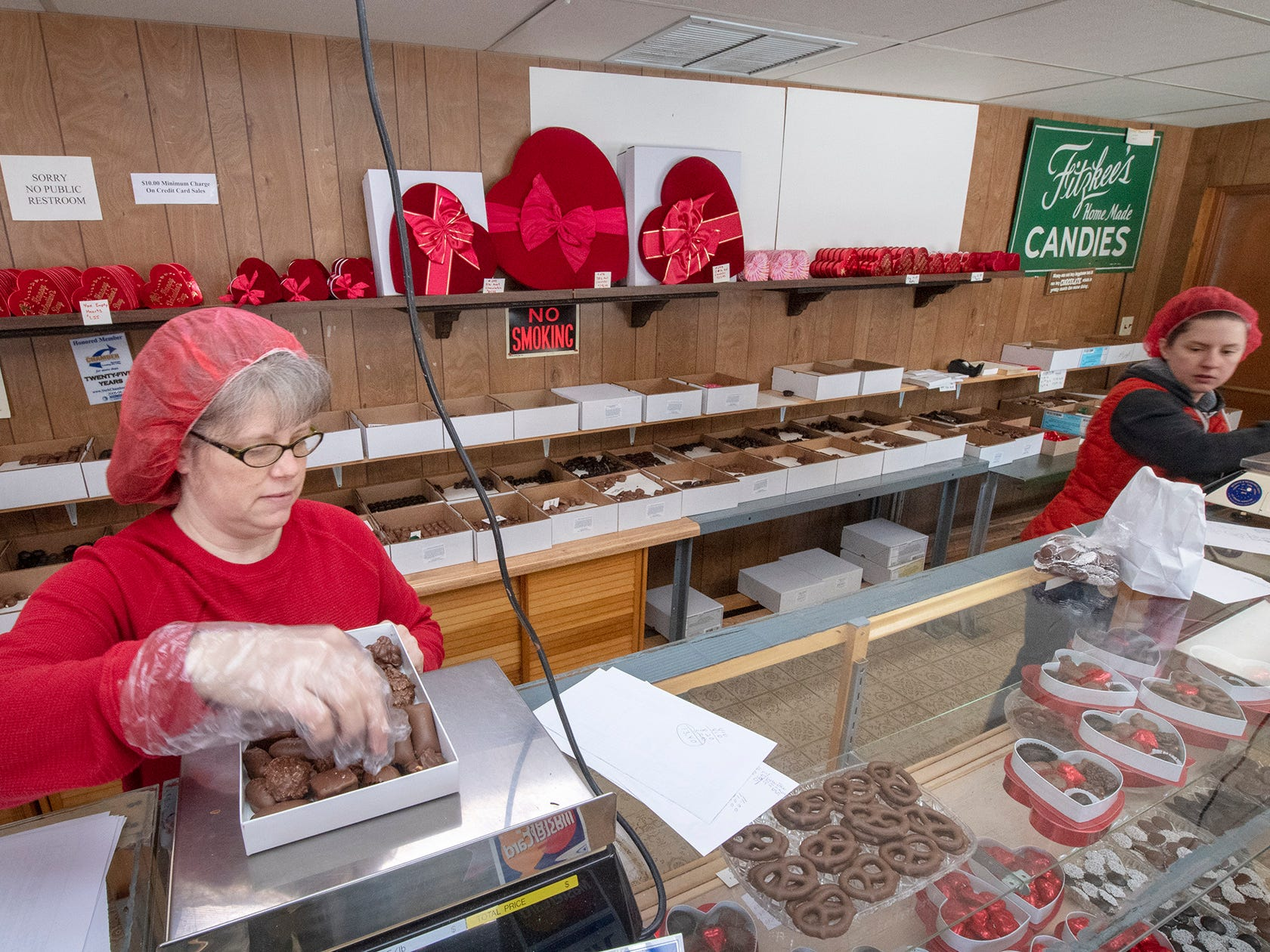 Local chocolate makers revved up for Valentine's Day. Here, Jennifer Long, left, packs a box of candies at Fitzkee's Candies Inc., 2352 S. Queen St. in York Township.