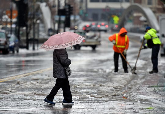 A women crosses a slushy Virginia Street as city workers clear the frozen snow from the crub so the water can freely move in downtown Reno on Wednesday Feb. 13, 2018.