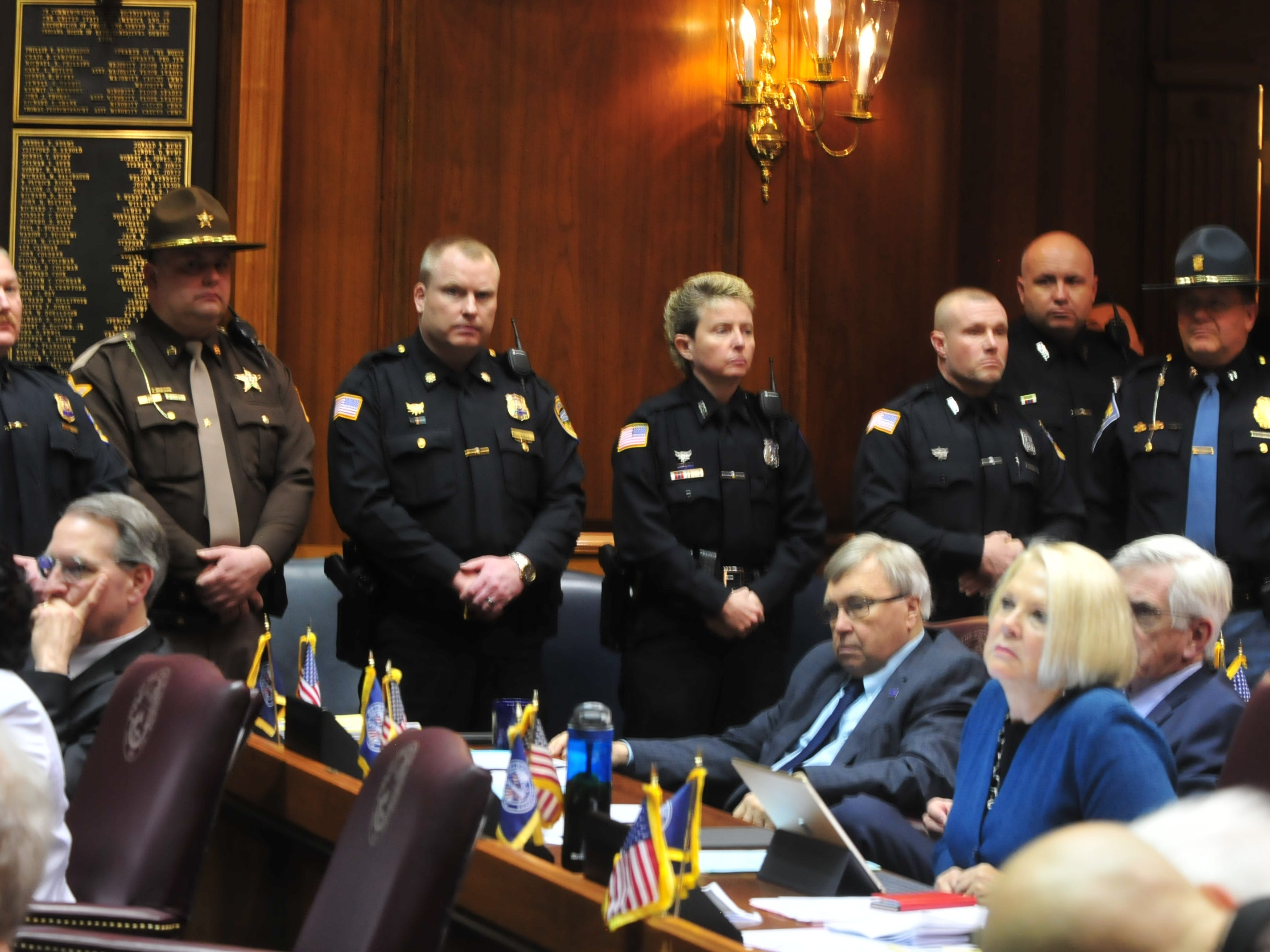 Richmond and Wayne County law enforcement officers stand inside the House chambers Tuesday in Indianapolis.