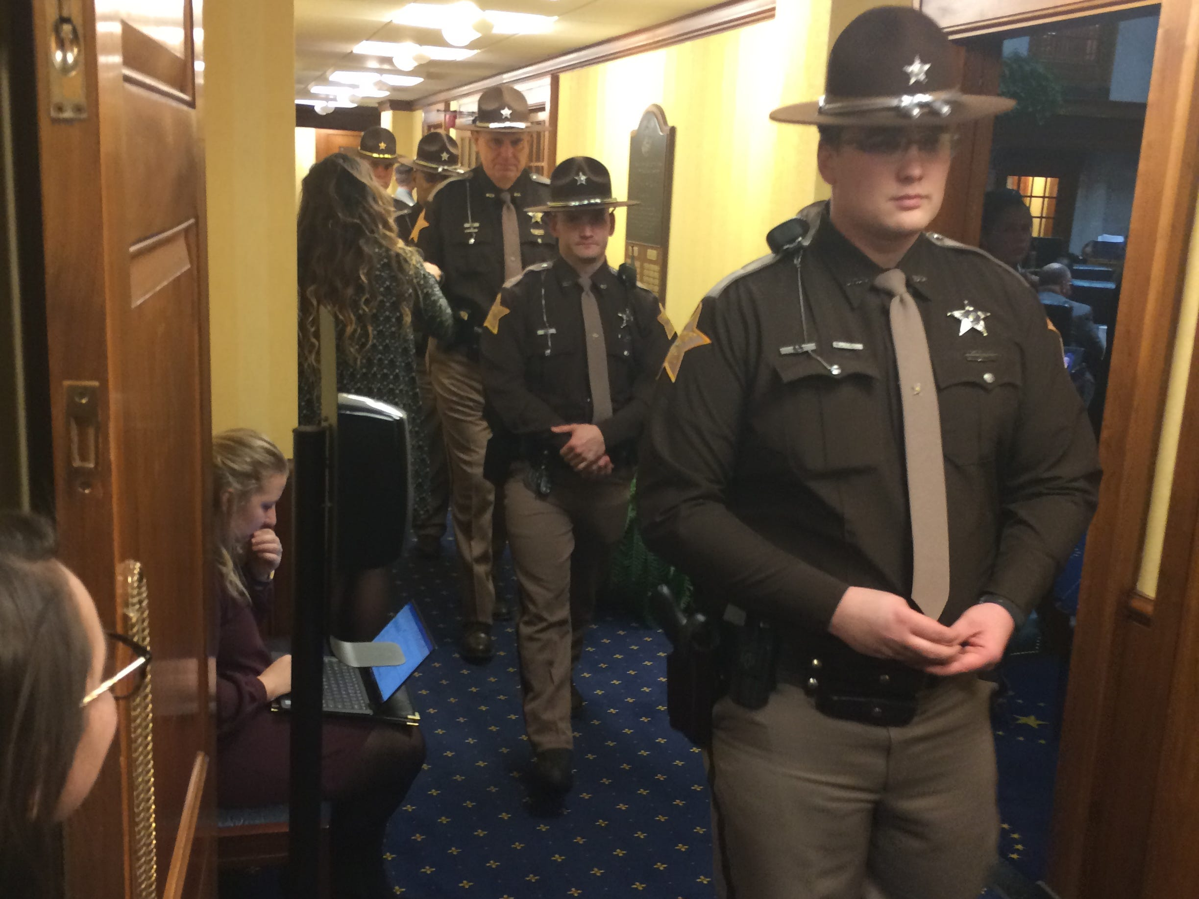 Law enforcement officers receive lapel pins in the shape of the state of Indiana as they leave the Senate chambers Tuesday.
