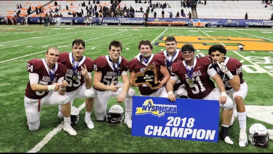 Aquinas tight end Steven Mahar Jr. (far right) poses with the team for Aquinas' state championship win.