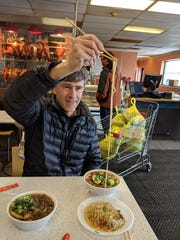 Michael Warren Thomas shows just how long the fu zhou noodles are.