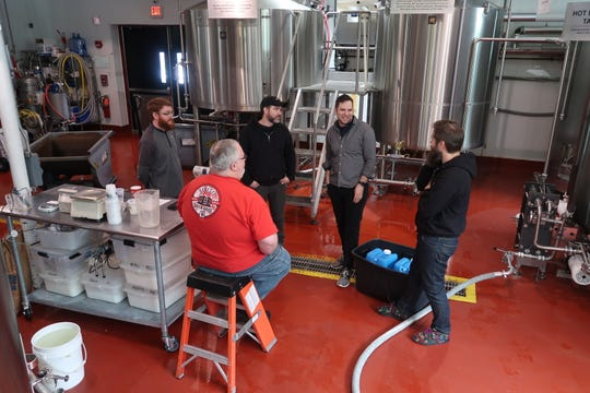 Genesee's Dean Jones, center, and Dan Kingsley, left, chat with the three founders of Other Half Brewing — Matt Monahan, center in hat, Andrew Burman, and Sam Richardson — during the brewery's collaborative brew day on Feb. 12.