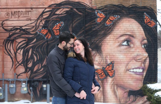 Rochester artist Justin Suarez with wife Kelly Suarez alongside the large mural he painted of her as a surprise, Wednesday, Feb. 13, 2019.  The 12-by-30 foot mural is on the side of HD Hair, at 2286 E. Main Street in Rochester.