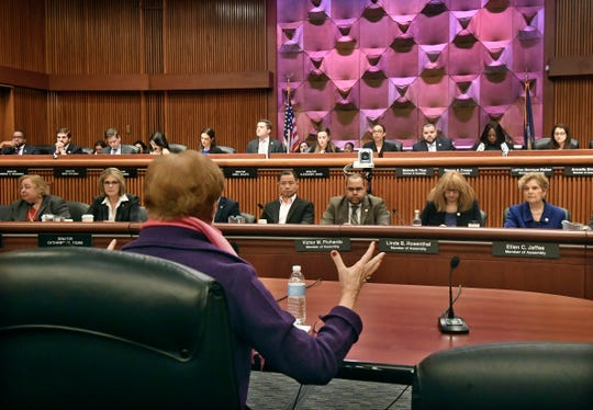 New York state Commissioner of Labor Roberta Reardon, back to camera, addresses state legislators during a public hearing on sexual harassment in the workplace Wednesday, Feb. 13, 2019, in Albany, N.Y.