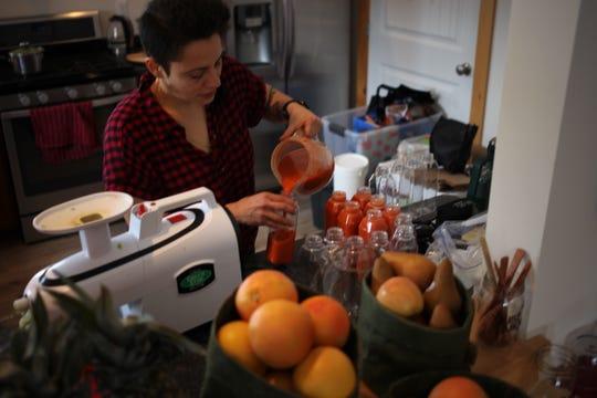 Damaris Pinedo fills bottles of juice at the Just Juice 4 Life Juice Retreat