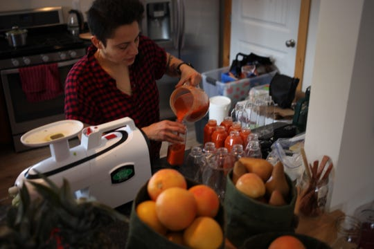 Damaris Pinedo fills bottles of juice at the Just Juice 4 Life Juice Retreat