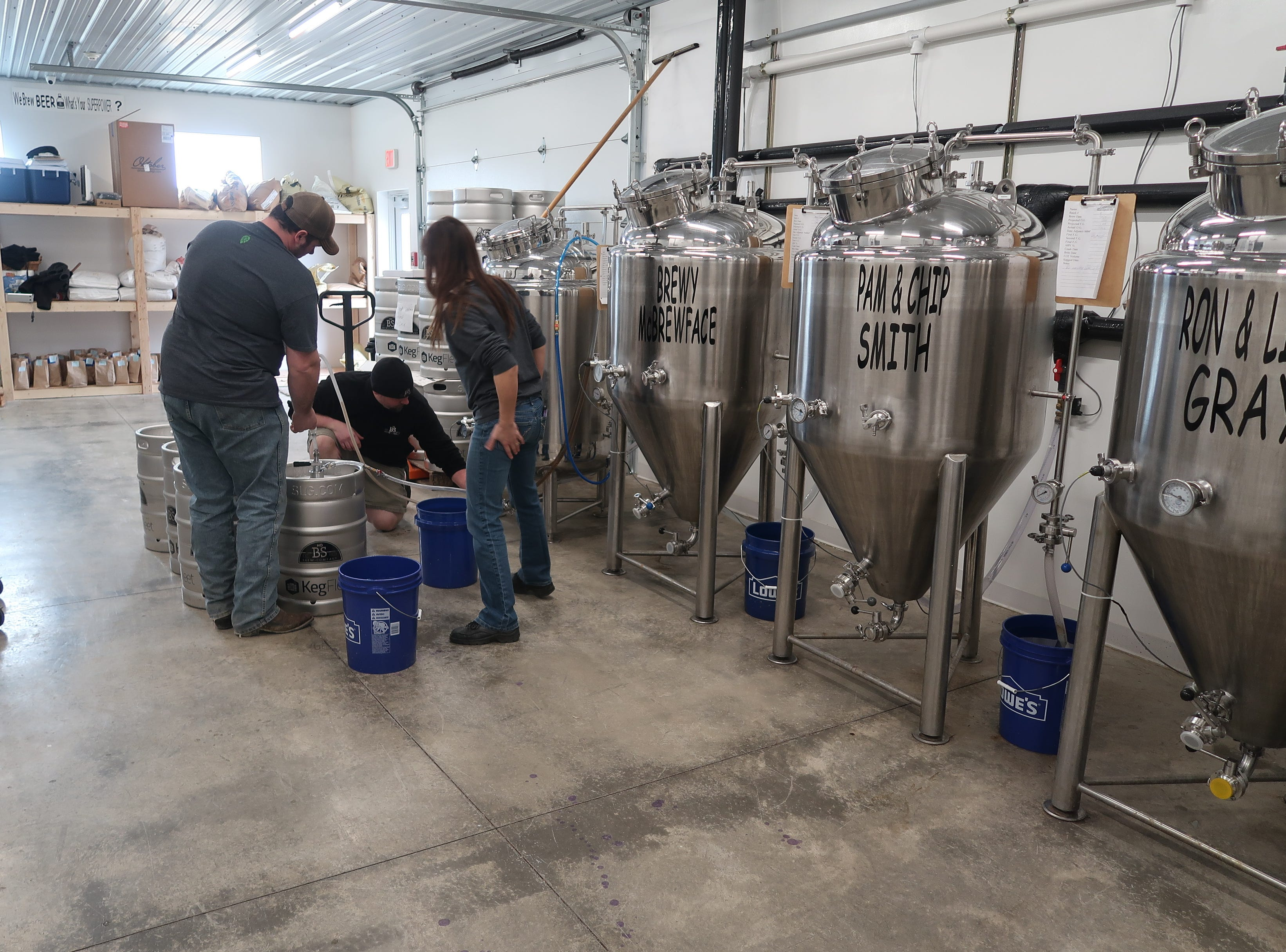 Owner and brewer Ben Noragong, center, gets ready to keg beer at No BS Brew Company in Livonia.
