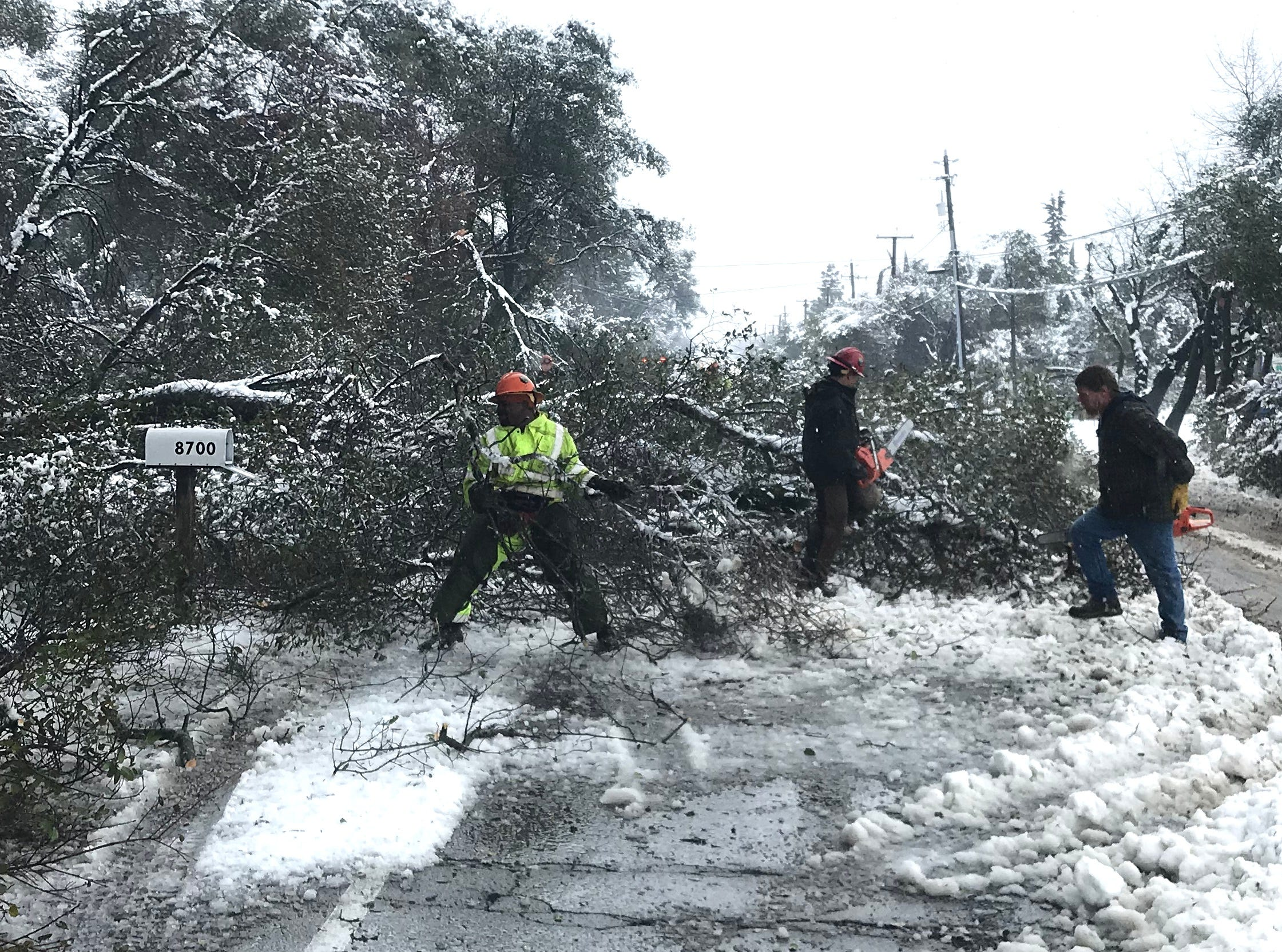 A crew clears branches from along Airport Road on Wednesday.