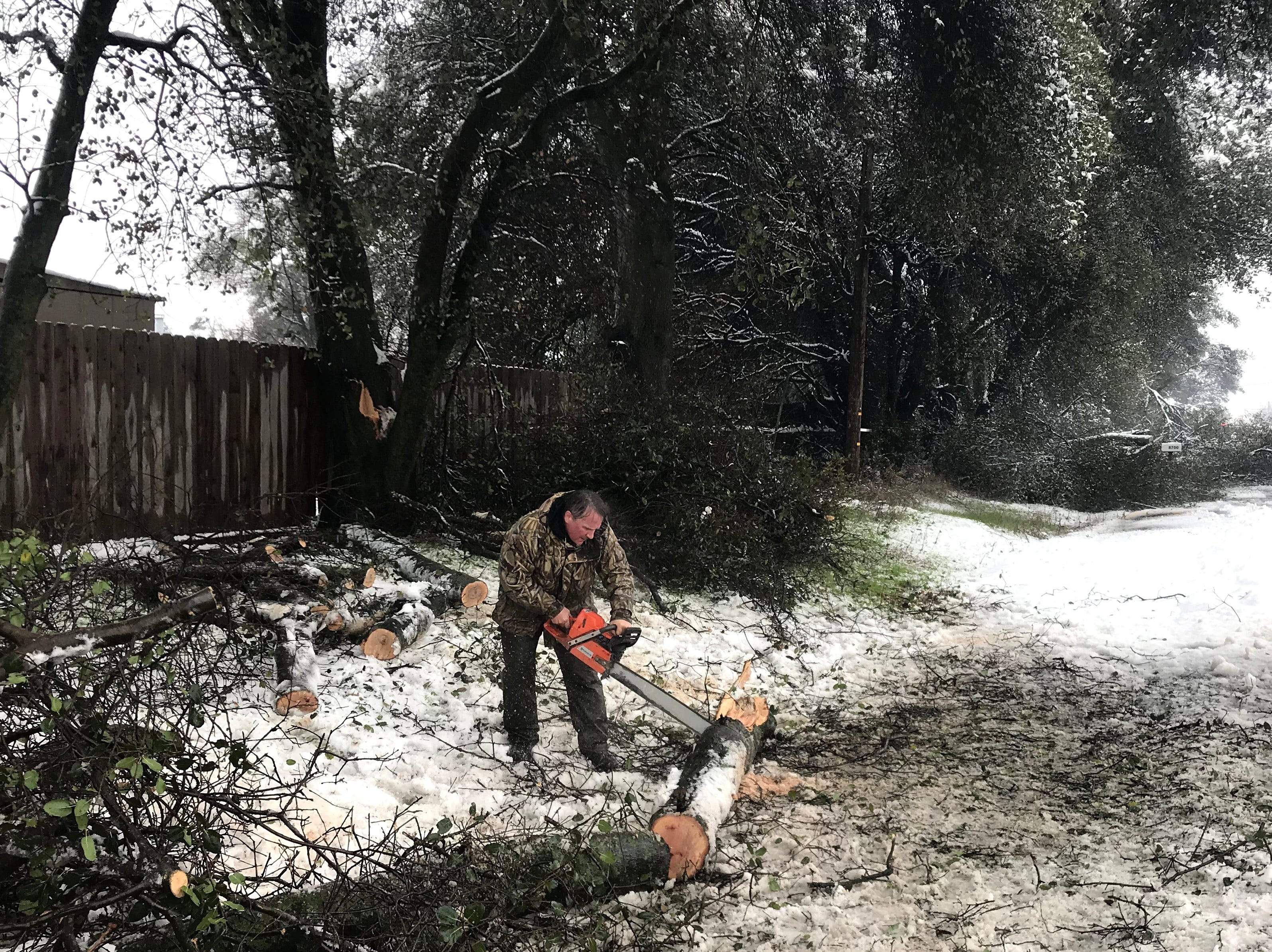 A man clears broken branches from alongside the road Wednesday.