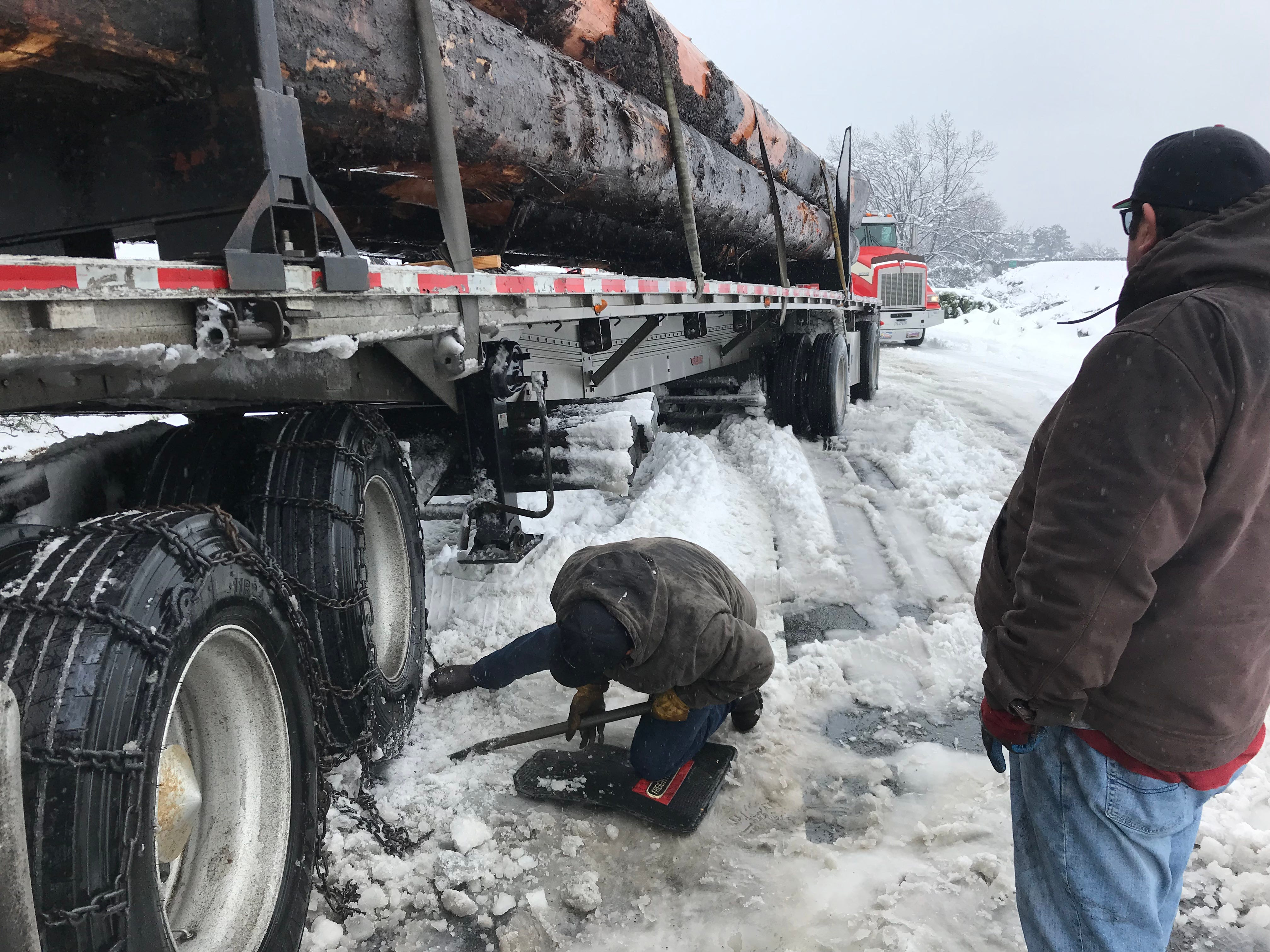 Truckers put chains on a truck stuck on the I-5 onramp in Anderson.