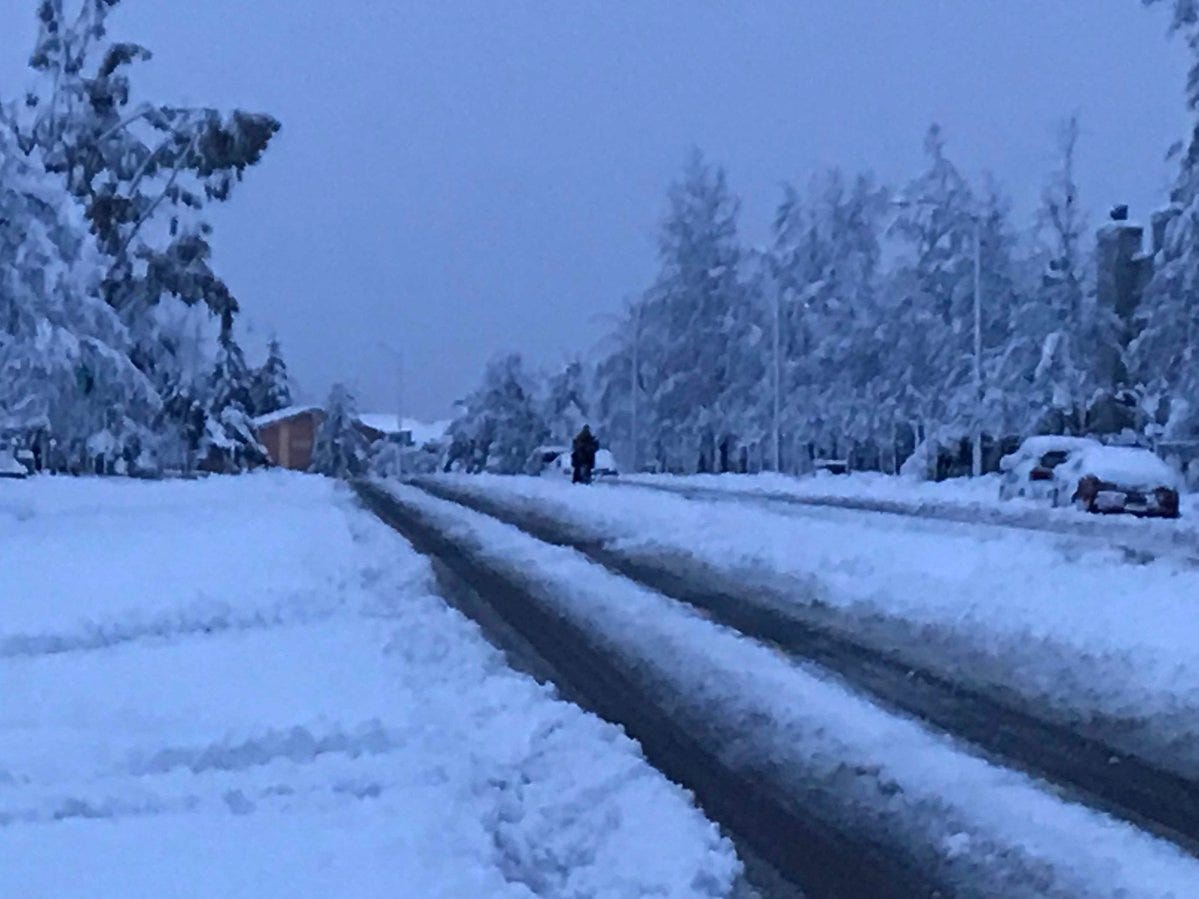 A pedestrian walks across Hilltop Drive Wednesday morning after 13 inches of snow hit Redding.