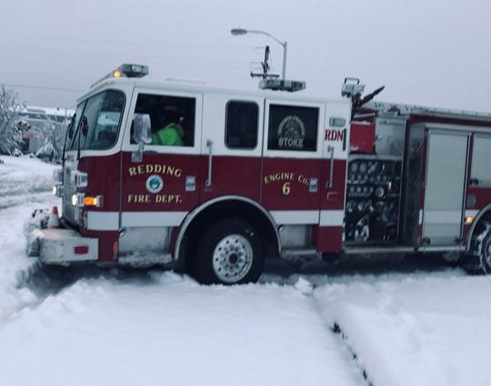 A Redding fire truck maneuvers through snow on the road on Wednesday, Feb. 13, 2019.