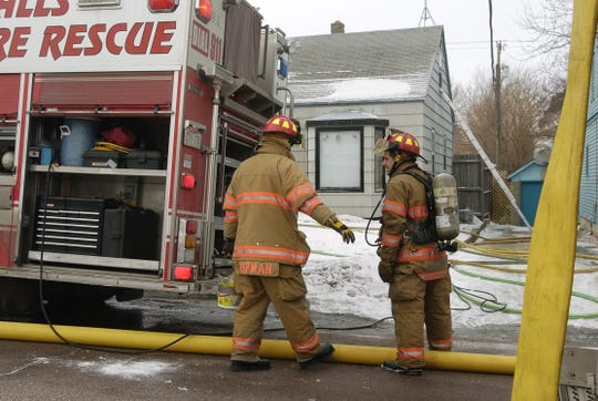 Sioux Falls firefighter Michael Koopman (left) prepares to spread ice melt after a fire in a mattress in a house on West Avenue near 12th Street in 2008.