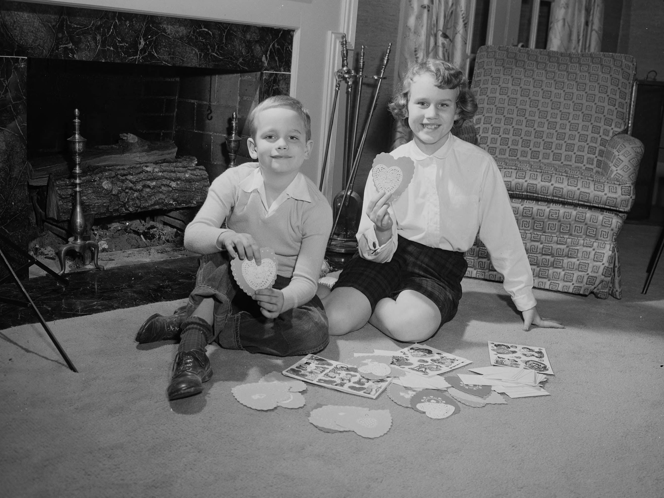 Ann Marie Brown and Bobby Brown sitting beside a fireplace with their Valentines in 1955.