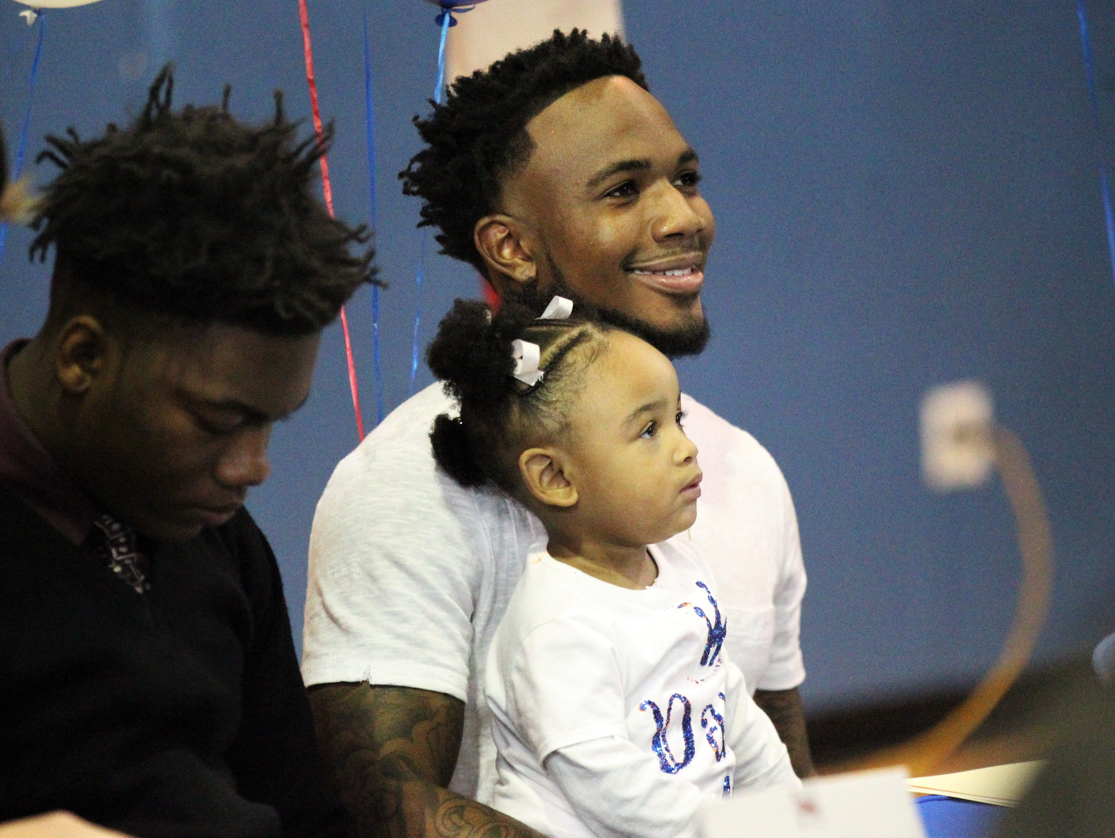 Jefferson County senior receiver Da'Shon Davis, with his nearly 2-year-old daughter De'ari, waits to sign with Tennessee State during Jefferson County's signing day ceremony on Feb. 13, 2019.