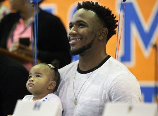 Jefferson County senior receiver Da'Shon Davis, with his daughter 9-month-old daughter Desire, waits to sign with Tennessee State during Jefferson County's signing day ceremony on Feb. 13, 2019.