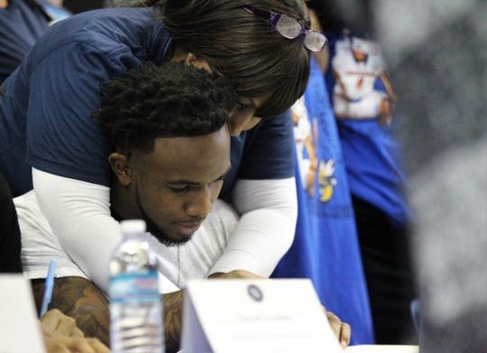 Jefferson County senior receiver Da'Shon Davis, with mother Malinda Williams around his neck, signs with Tennessee State during Jefferson County's signing day ceremony on Feb. 13, 2019.