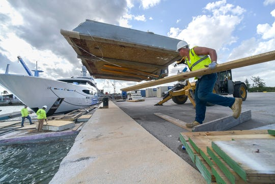 Stephen Grant (right) of Scaffold Shrinkwrap, of Pompano Beach, carries boards to help his coworkers Damion Bowen (left) and Aaron Neal as they install fiberglass and styrofoam floats surrounding the mega-yacht Vibrance, on Tuesday, Feb. 12, 2019, as part of Fort Pierce Yacht & Ship LLC's 3-month long $1 million repainting project for the ship, docked at the Port of Fort Pierce. Metal scaffolding and shrinkwrap will surround the yacht to provide a protected environment for paint crews to work.