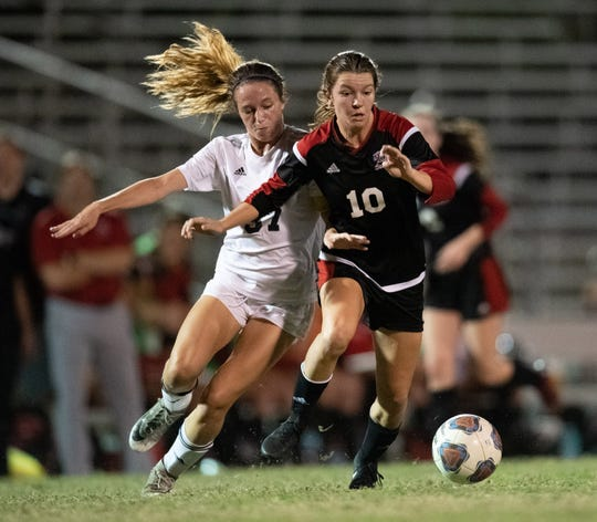Vero Beach's Madelaine Rhodes (right) battles for possession of the ball against  Boca Raton in the first half of their regional championship game at Vero Beach High School's Citrus Bowl on Tuesday, Feb. 12, 2019, in Vero Beach.