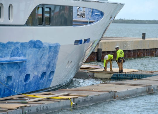 Aaron Neal (left) and Dario Lewis, of Scaffold Shrinkwrap of Pompano Beach, secure together fiberglass and styrofoam floats surrounding the mega-yacht Vibrance on Tuesday, Feb. 12, 2019, as part of Fort Pierce Yacht & Ship LLC's 3-month long $1 million project repainting the ship docked at the Port of Fort Pierce.