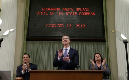 California Gov. Gavin Newsom, center, flanked by Assembly Speaker Anthony Rendon, D-Lakewood, left, and Senate President Pro Tem Toni Atkins, D-San Diego, right, applauds Camp Fire survivor Allyn Pierce during Newsom's  first State of the State address to a joint session of the Legislature in Sacramento.