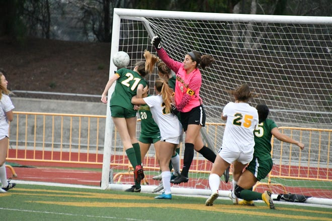 Moorpark High goalkeeper Felicia Neatherlin punches a cross clear against Manhattan Beach-Mira Costa on Tuesday night in the CIF-Southern Section Division 2 quarterfinals. Jessica Rodriguez (21) also attempts to clear the ball for Moorpark. Mira Costa won, 3-2.