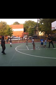 Former Wilmington City Councilman Nnamdi Chukwuocha snapped this picture in 2012 of Cpl. Thomas Oliver (right) and Cpl. Jamaine Crawford playing basketball with children at Helen Chambers Park. Wilmington police say Oliver raped a woman while on duty about five years later.