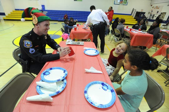 Senior Corporal Thomas Oliver (left) with the Wilmington Police Department shows a magic trick during the department's first-ever breakfast for the youth at West Center City's Hicks Anderson Center in December 2015.