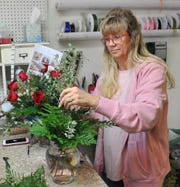 Jameson's Flowers designer Lori Jameson works on an arrangement of roses Wednesday as she and daughter, Jenny Lee Hines prepare for the busy Valentine season. Lori and husband David Jameson turned over the business to Jenny and her husband Bryan this summer.