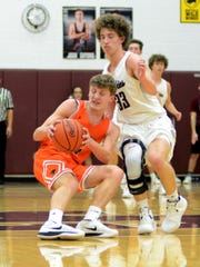 New Lexington's Logyn Ratliff is guarded closely by John Glenn's Evan Williams during their game on Tuesday in New Concord. The Muskies won, 54-31.