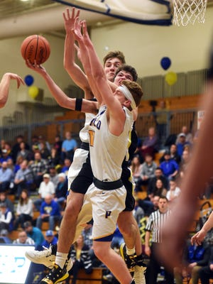 Tri-Valley's Keaton Williams draws contact in the lane from Philo's A.J. Clayton, left, and Austen Bonifant during a shot in the second quarter of their game on Tuesday in Philo. Tri-Valley won the game, 42-41, in overtime to keep its Muskingum Valley League title chances alive.