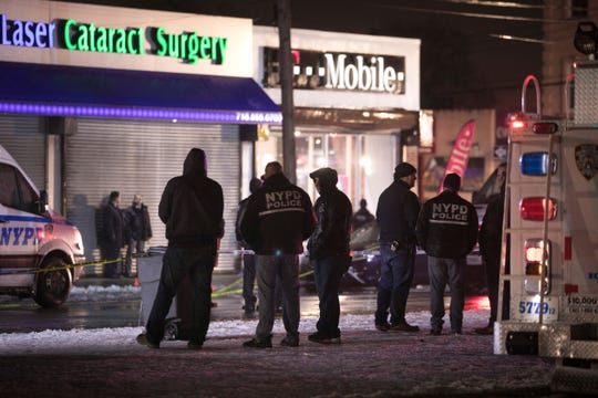 Investigators look over the area after a few New York City police officers were shot while responding to a robbery at a T-Mobile store in the Queens borough of New York on Tuesday, Feb. 12, 2019.