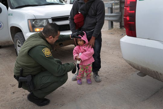 A Border Patrol agent speaks with Central American immigrants after they crossed the border from Mexico on on Feb. 1, 2019, in El Paso, Texas.