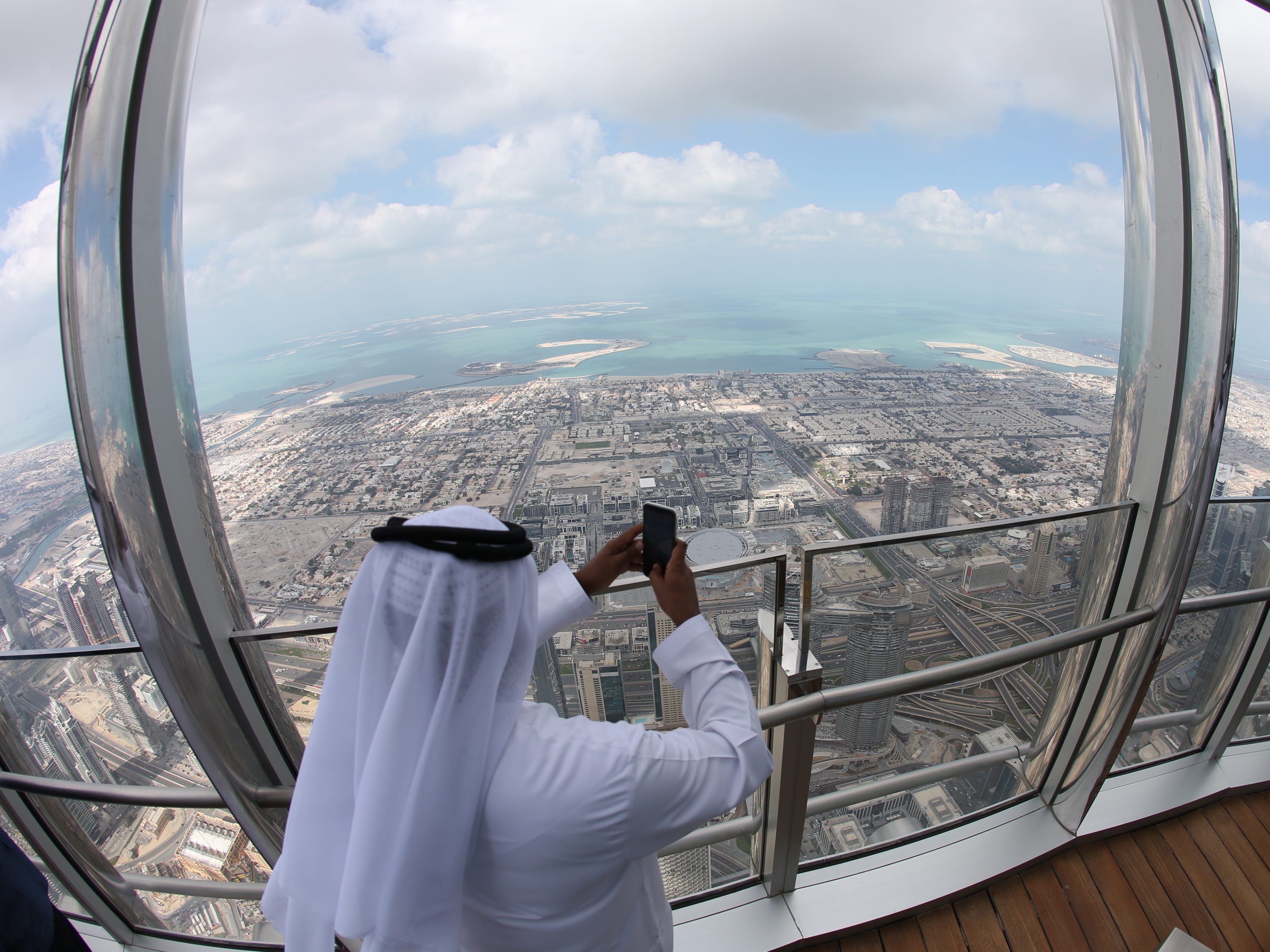epa07366683 A picture taken with a fish eye lens shows UAE man taking photo from the new highest lounge in the world at Burj Khalifa in Dubai, United Arab Emirates, 13 February 2019. Ahmad Al Falasi, Executive Director Emaar Properties announced during media briefing the opening of highest lounge in the world at Burj Khalifa which is located at 152, 153 and 154 floor which have distinctive settings each assuring never before seen views of the city.  EPA-EFE/ALI HAIDER ORG XMIT: XAH001