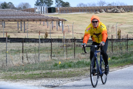 A man rides his bicycle by the Whitt facility for Southern Current solar  power on Thursday, February 14, 2019.