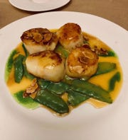 Diver scallops with snow peas, orange ginger butter and roasted almonds at from Oldwick General Store.