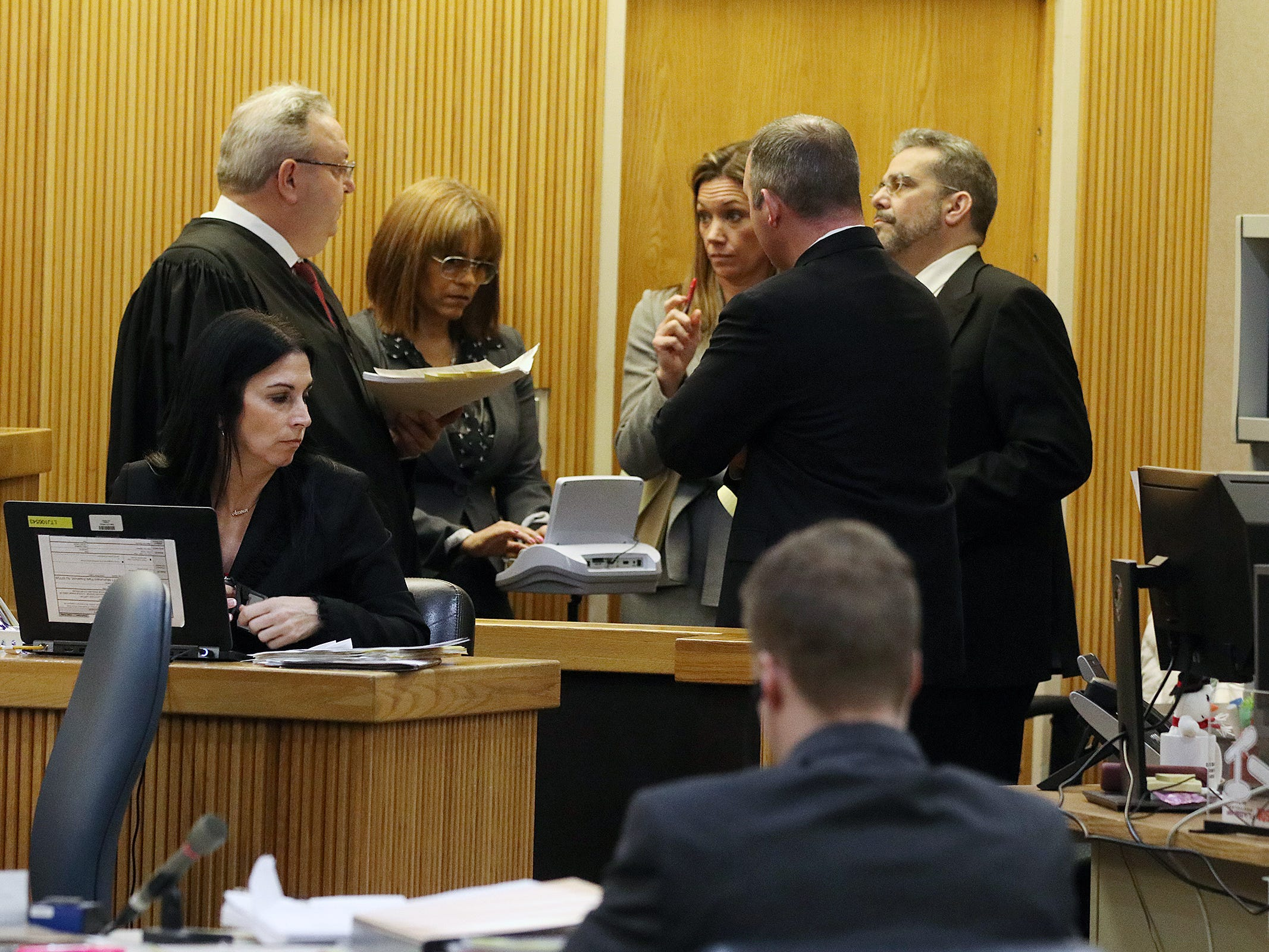 Liam McAtasney, who is charged with the murder of former high school classmate, Sarah Stern, listens as Superior Court Judge Richard W. English and attorneys during a sidebar during trial at the Monmouth County Courthouse in Freehold, NJ Thursday, February 14, 2019. The judge was considering a motion from the defense for a mistrial after it was discovered that two jurors, who were later dismissed, were communicating on Facebook Messenger.