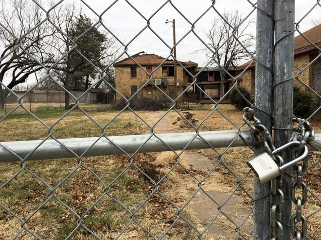 The chain-link fence surrounding St. Ann Hospital is locked to protect the property from further damage.