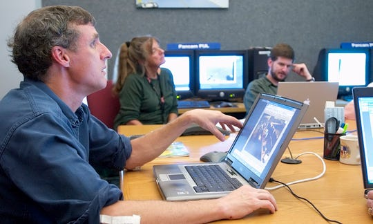 Cornell professor Steven Squyres leads the daily Science Operations Working Group meeting held via a web video conference as they oversee a Mars Rover mission in 2006. In the background are Mission Specialist Elaina McCartney, and Research Support Specialist Dale Theiling.