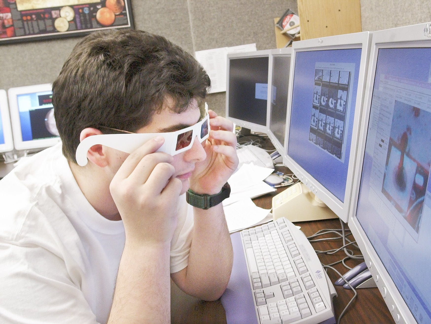 "John Roma ""J.R."" Skok uses a pair of 3-D glasses to check out a calibration target image while waiting for data to come in from the Mars Rover Spirit at Cornell University in 2004."
