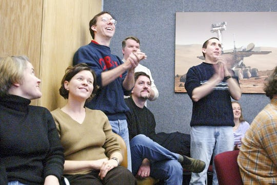 From left, Maria Barry, Jennie Romney, Don Banfield, Larry Klaes, Tom Balon and Anthony Toigo celebrate the safe landing of the Mars Rover Spirit on Jan. 4, 2004 at the Space Sciences building at Cornell University. They were watching a live feed from mission control in Pasadena, Calif.