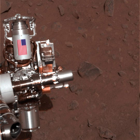This image provided by NASA shows the piece of metal with the American flag on it is made of aluminum recovered from the site of the World Trade Center towers in New York City on Mars Rover Spirit that serves as a cable guard for Spirit's rock abrasion tool as well as a memorial to the victims of the Sept. 11, 2001, terrorist attacks. Mars Rover Opportunity has an identical piece. Ten years after NASA landed two rovers on Mars on a 90-day mission, one rover is still exploring, and the project has generated hundreds of thousands of images from the Martian surface. Now the Smithsonian's National Air and Space Museum is presenting more than 50 of the best photographs from the two Mars rovers in an art exhibit curated by the scientists who have led the ongoing mission. (AP Photo/NASA/JPL-Caltech/Cornell University)