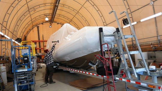 Finisher Garrett Whisenant shrink wraps a boat to get it ready for delivery at SAFE boats in Bremerton on Thursday, February 14, 2019.
