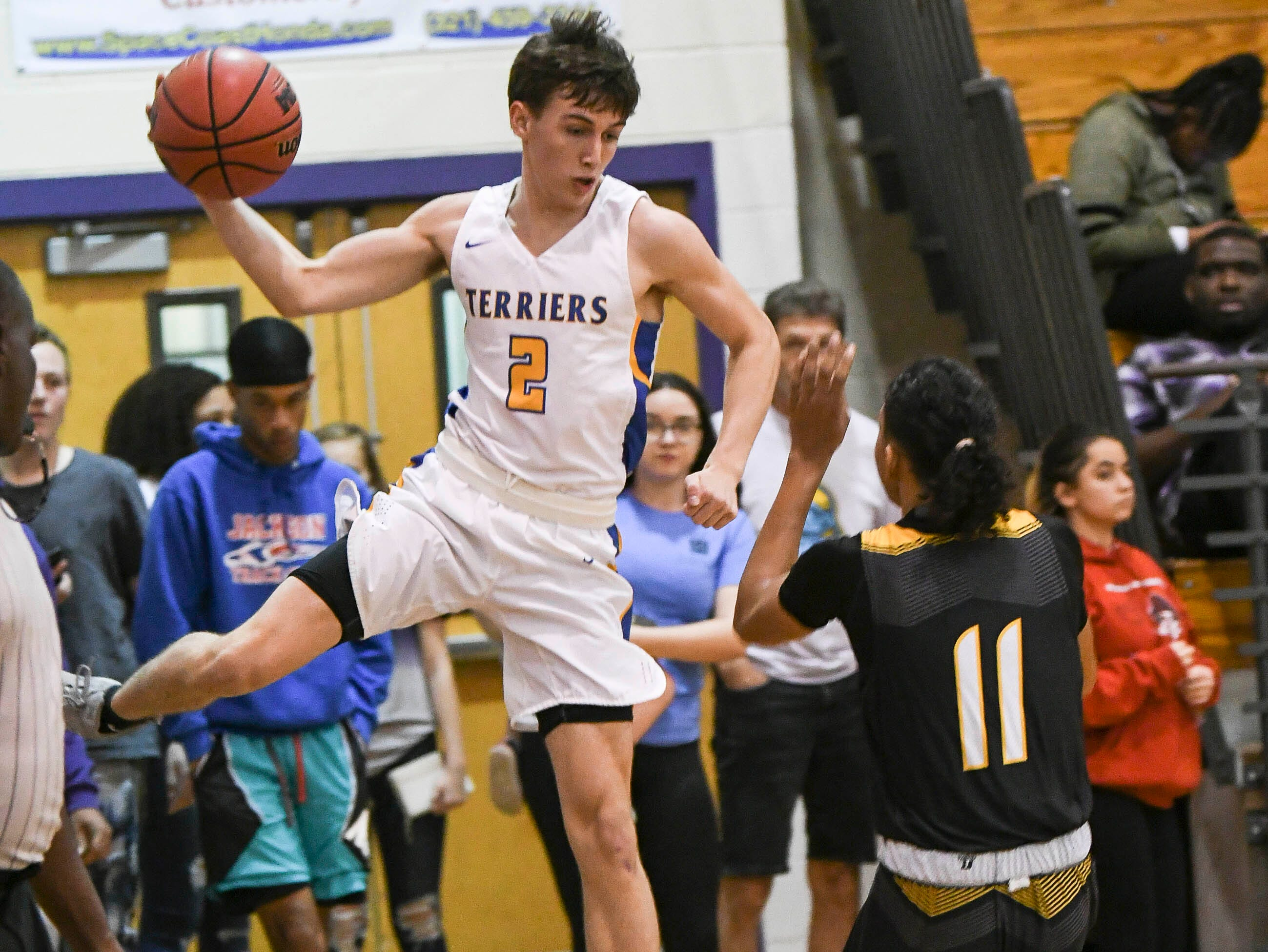 Blaine Reid of Titusville throws the ball out of bounds off EJ Balk of Merritt Island during Tuesday's District 14-6A boys basketball tournament.