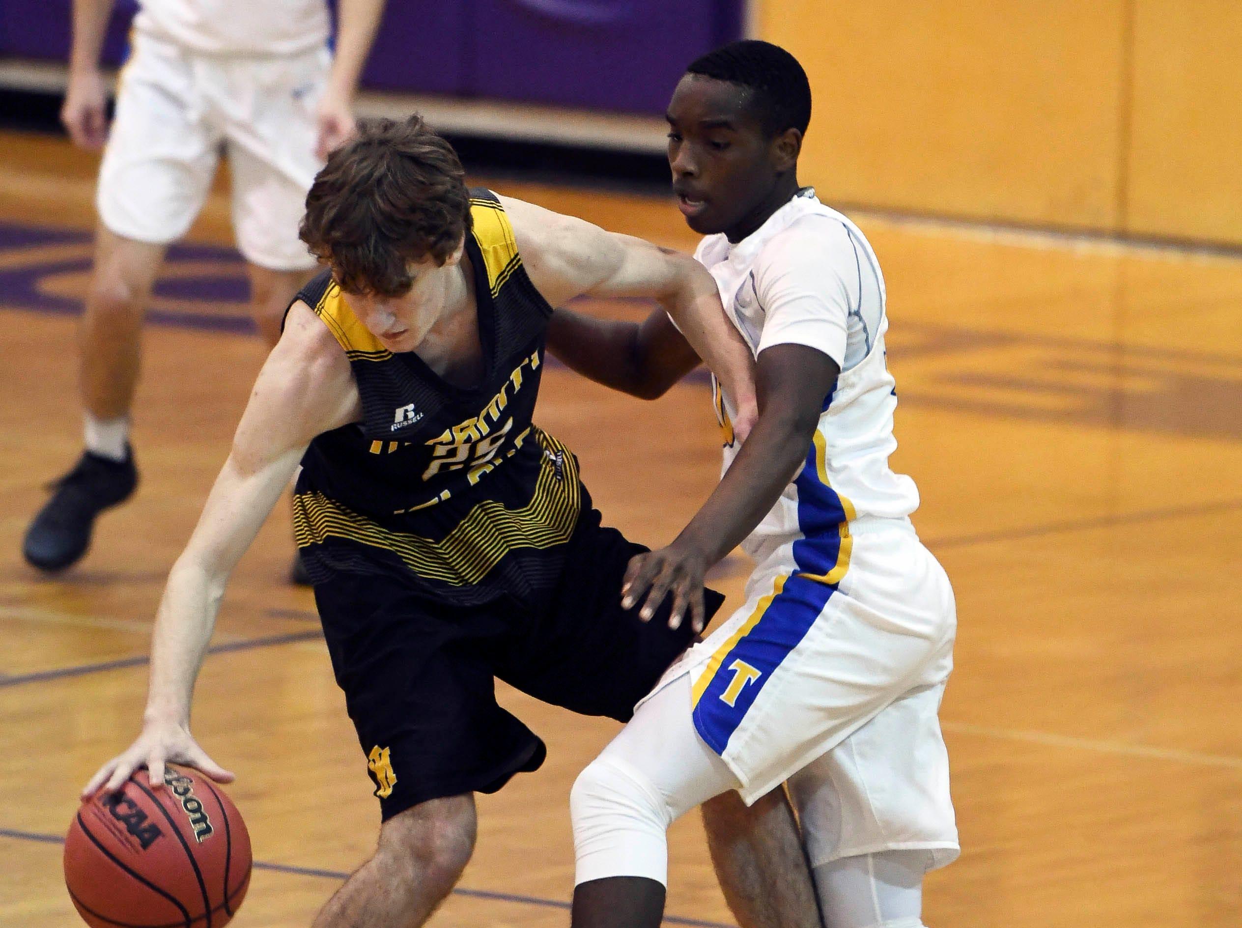 John Michael Zepp of Merritt Island keeps Keivn Brooks of Titusville from stealing the ball during Tuesday's District 14-6A boys basketball tournament