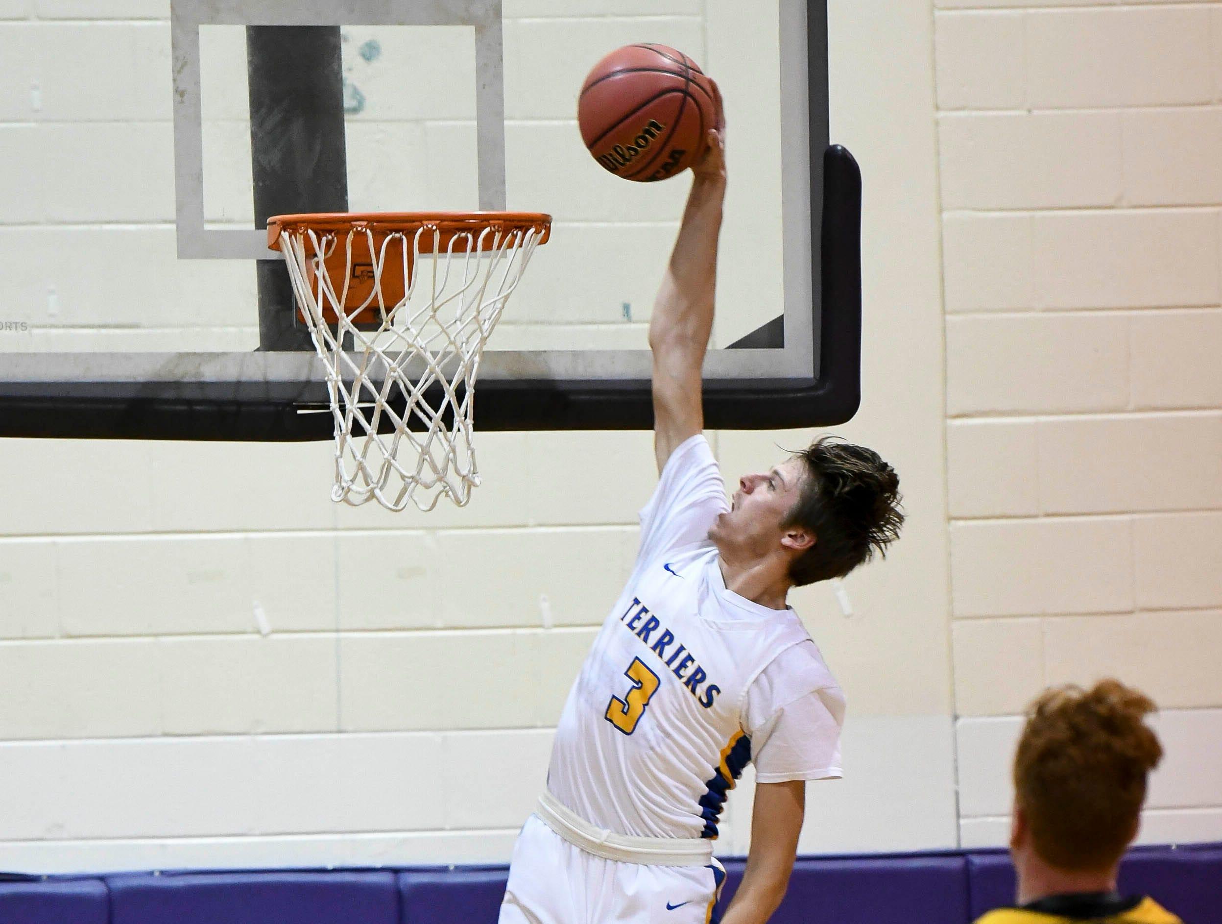 Titusville's Trent Cunningham dunks the ball during Tuesday District 14-6A boys basketball tournament game against Merritt Island.