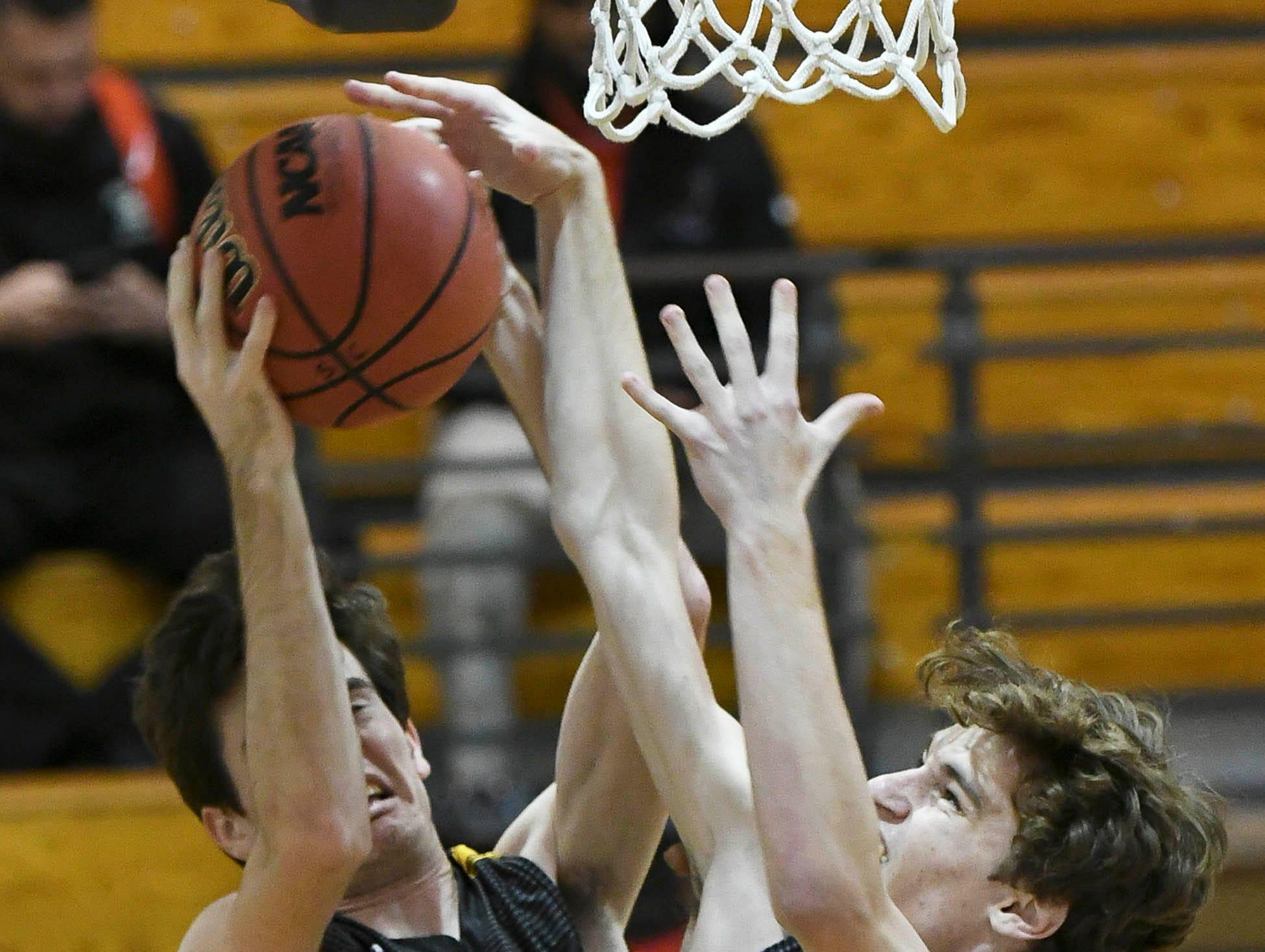 John Michael Zepp and Hayden Wall of Merritt Island rebound the ball during Tuesday's District 14-6A boys basketball tournament.